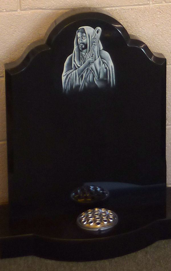 Polished black granite headstone with inlay